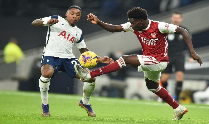 Bergwijn y Saka luchan por el balón en la imagen. Revisa las mejores cuotas para el Arsenal vs Tottenham una lucha