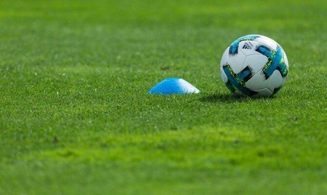 Un balón y un cono sobre el césped en la imagen. Cuotas y picks Racing Club vs Boca Juniors.